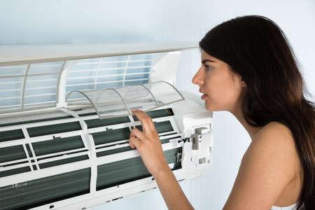 Foto de Young Woman Checking Air Conditioner In House - Imagen libre de derechos