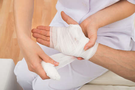 Photo pour High Angle View Of A Female Doctor Bandaging Patient's Hand - image libre de droit