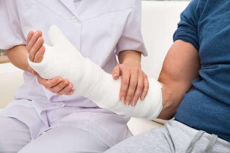 Foto de Close-up Of A Female Doctor Holding Fractured Hand Of A Patient - Imagen libre de derechos