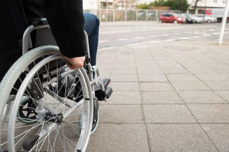 Foto de Close-up Of Disabled Man Sitting On Wheelchair - Imagen libre de derechos