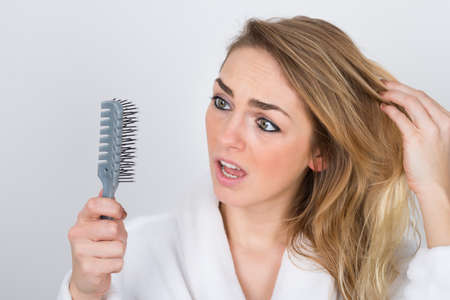 Foto de Worried Woman Suffering From Hairloss Looking At Comb - Imagen libre de derechos