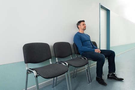 Foto de Portrait Of A Mid-adult Man Sitting On Chair In Hospital - Imagen libre de derechos