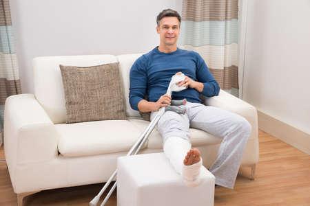 Foto de Portrait Of A Smiling Man Sitting On Sofa With Crutches At Home - Imagen libre de derechos