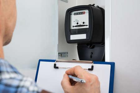 Foto de Technician Writing Reading Of Meter On Clipboard - Imagen libre de derechos
