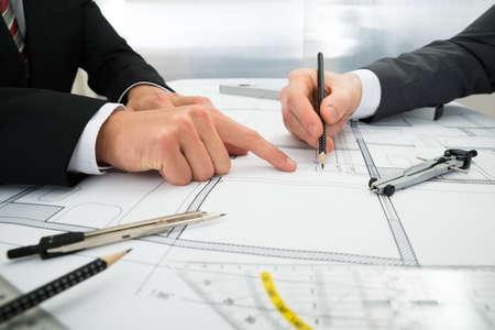 Foto de Close-up Of Two Architects Planning Project On Blueprint - Imagen libre de derechos