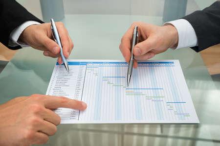 Foto de Close-up Of Two Businessman With Gantt Diagram At Desk - Imagen libre de derechos