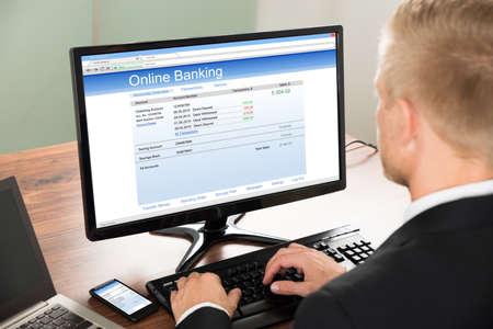Foto de Close-up Of A Businessman Using Online Banking Service On Computer At Office - Imagen libre de derechos
