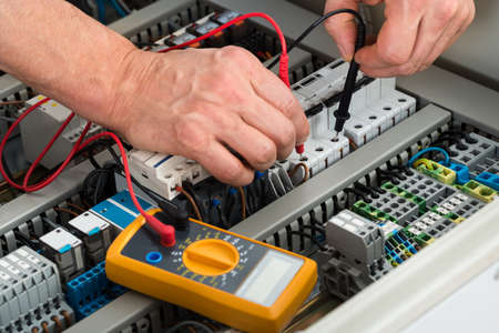 Foto de Close-up Of A Male Electrician Checking Fuse With Multimeter - Imagen libre de derechos