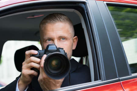 Photo pour Close-up Of A Male Driver Photographing With Slr Camera From Car - image libre de droit