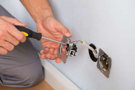 Foto de Close-up Of Electrician Hands With Screwdriver Installing Wall Socket - Imagen libre de derechos