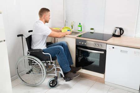 Foto de Young Disabled Man On Wheelchair Washing Dishes In The Kitchen - Imagen libre de derechos