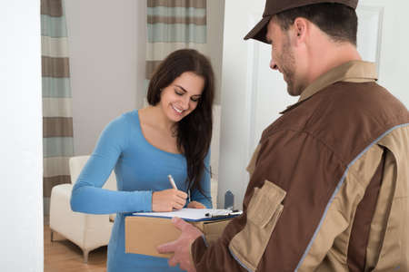 Photo pour Young Woman Signing While Receiving Courier From Delivery Man At Home - image libre de droit