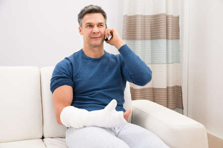 Foto de Man With Fractured Hand Sitting On Sofa Talking On Cellphone - Imagen libre de derechos