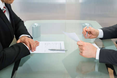 Photo for Businessman Conducting An Employment Interview With Application Form On Office Desk - Royalty Free Image