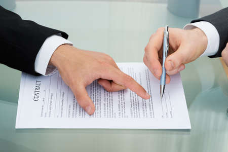 Photo for Person Pointing On Paper To Sign On Contract - Royalty Free Image