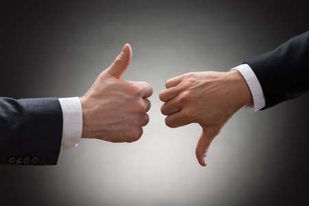 Photo for Close-up Of Two Businesspeople Hands Showing Thumb Up And Thumb Down Sign - Royalty Free Image