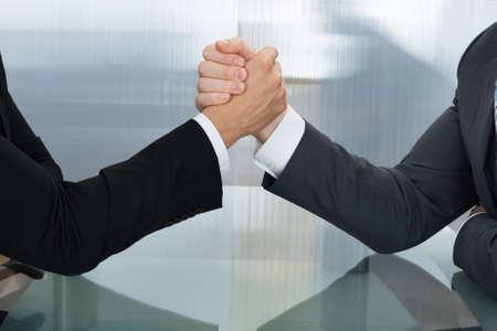 Foto de Two Businessman Holding Each Other Hands Over Desk In The Office - Imagen libre de derechos