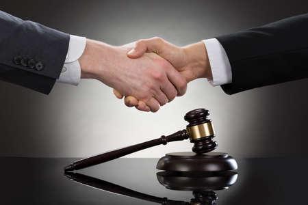Photo pour Close-up Of Two Businessman Shaking Hands In Front Of Mallet - image libre de droit