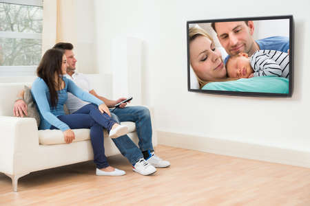 Photo pour Young Couple In Livingroom Sitting On Couch Watching Television - image libre de droit
