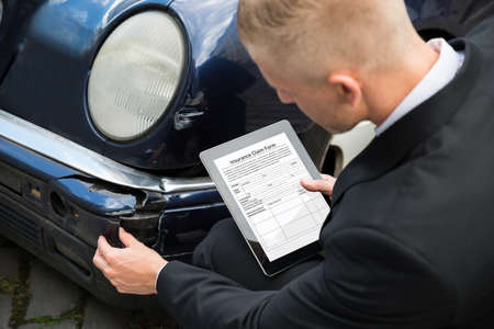 Photo pour Insurance Agent Inspecting Damaged Car With Insurance Claim Form On Digital Tablet - image libre de droit