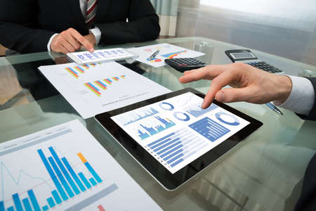 Photo pour Close-up Of Two Businessman Analyzing Graph On Digital Tablet - image libre de droit