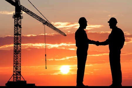 Photo pour Silhouette Of Two Architect At Construction Site Shaking Hand - image libre de droit