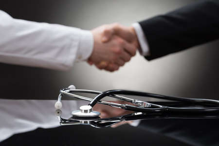Foto de Doctor And Businessman Shaking Hand In Front Of Stethoscope - Imagen libre de derechos