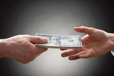 Photo pour Close-up Of Person Hand Giving Money To Other Hand - image libre de droit