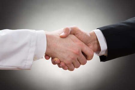 Foto de Close-up Of A Doctor And Businessman Shaking Hand - Imagen libre de derechos