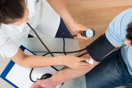 Foto de Close-up Of Female Doctor Checking Blood Pressure Of Male Patient - Imagen libre de derechos