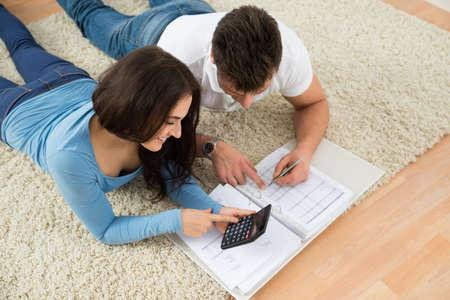 Photo pour Portrait Of A Happy Young Couple Lying On Rug Calculating Invoice - image libre de droit