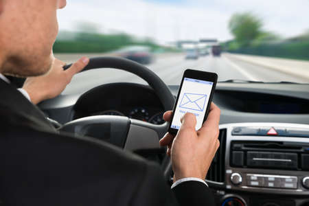Photo for Close-up Of A Man Holding Cellphone With Message Notification While Driving Car - Royalty Free Image