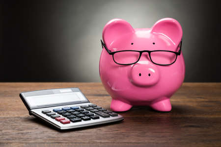 Photo pour Pink Piggybank With Calculator On Wooden Table - image libre de droit