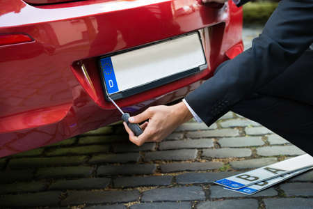 Photo pour Man Placing New Empty White Number Plate On His Red Car - image libre de droit