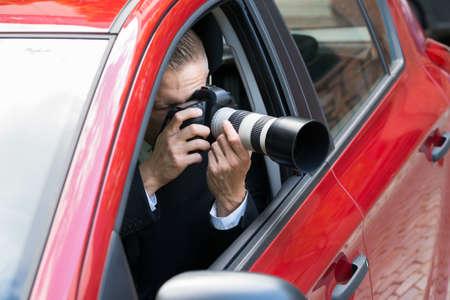 Foto de Close-up Of A Male Driver Photographing With Slr Camera From Car - Imagen libre de derechos