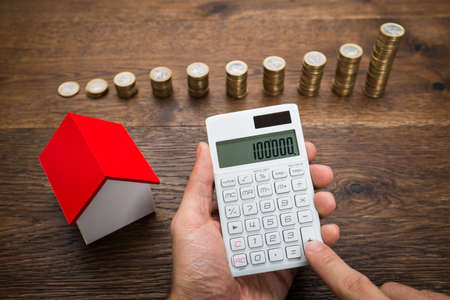 Photo pour Businessman Using Calculator With House Model And Stack Of Coins On Desk - image libre de droit