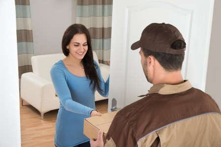 Photo for Smiling Young Woman Receiving Courier From Delivery Man At Home - Royalty Free Image