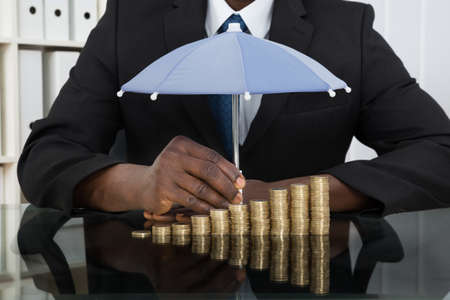 Photo pour Close-up Of Businessman Protecting Stack Of Coins With Umbrella At Desk - image libre de droit