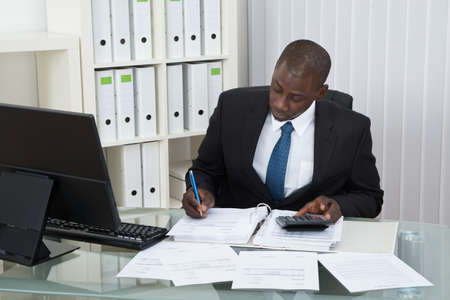 Photo pour Young African Businessman Calculating Finance Bills In Office - image libre de droit
