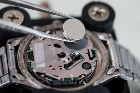 Photo pour Close-up Of Tweezers Placing Battery On Silver Wrist Watch - image libre de droit