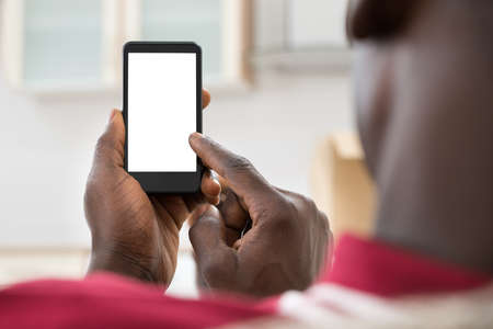 Photo pour Close-up Photo Of  African Man Holding Cellphone - image libre de droit