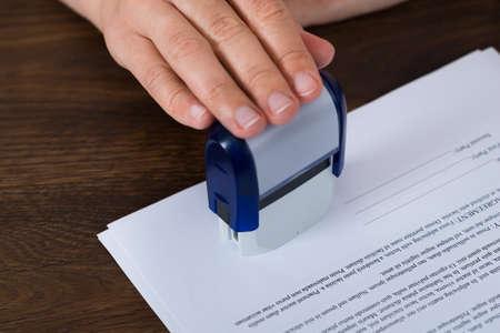 Photo pour Close-up Of Person Hands Stamping Document At Desk - image libre de droit