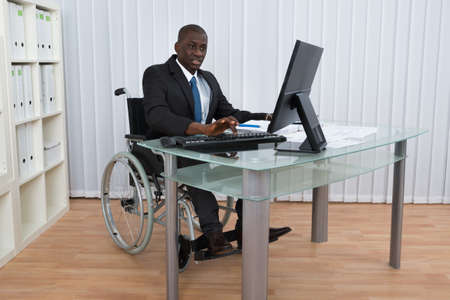 Foto de Portrait Of Happy African Businessman Working In Office Sitting On Wheelchair - Imagen libre de derechos