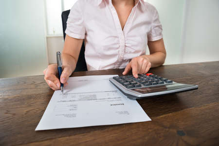 Close-up Of Female Businesswoman Calculating Tax With Calculator At Desk