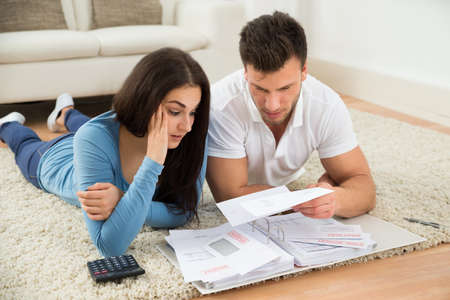 Photo pour Worried Young Couple Lying On Carpet Calculating Their Bills At Home - image libre de droit