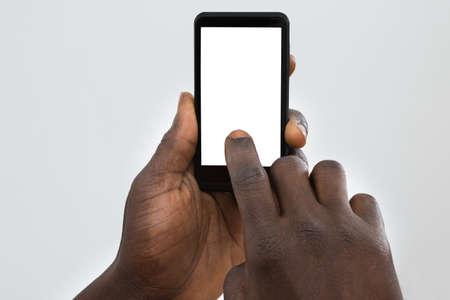 Foto de Close-up Of Person's Hand Using Cellphone With Blank Screen - Imagen libre de derechos