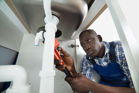 Foto de Young African Handyman Repairing Sink Pipe With Worktool - Imagen libre de derechos