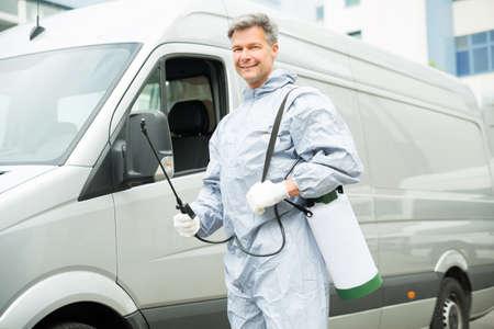 Foto de Happy Worker With Pesticide Sprayer Standing In Front Van - Imagen libre de derechos