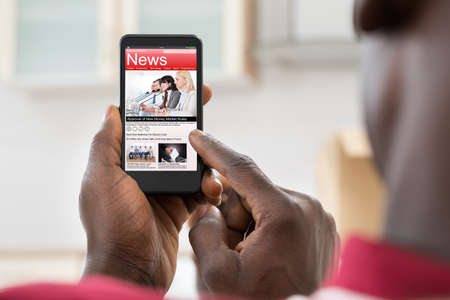 Photo for Close-up Of African Young Man Reading News On Smartphone - Royalty Free Image