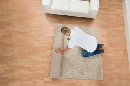 Photo for Young Man Unrolling Carpet In Living Room - Royalty Free Image